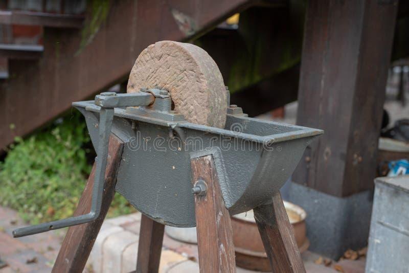 削尖的刀子一块老磨刀石 在老砂轮 图库摄影