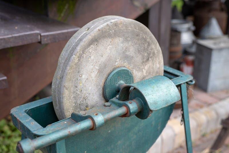 削尖的刀子一块老磨刀石 在老砂轮 库存照片