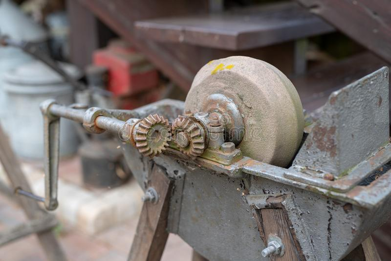 削尖的刀子一块老磨刀石 在老砂轮 免版税库存照片