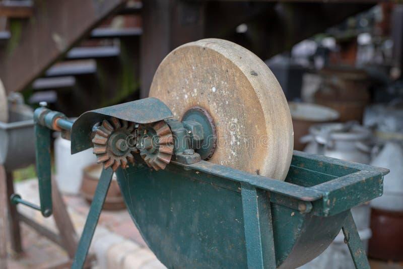 削尖的刀子一块老磨刀石 在老砂轮 免版税库存图片