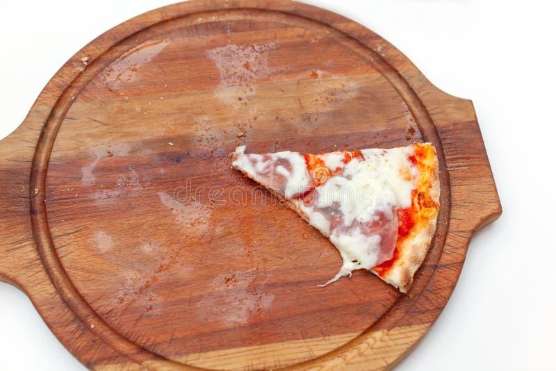 前一个切片可口意大利比萨用火腿和乳酪在木板在白色桌上 比萨时间 r r 免版税库存照片