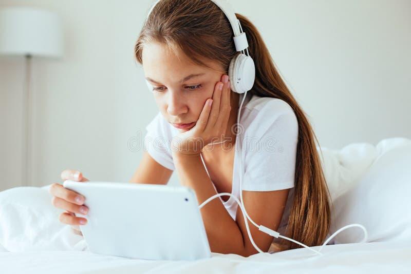 前使用片剂个人计算机的青少年的女孩 免版税库存照片