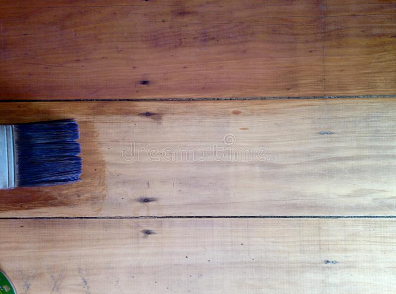 以前弄脏杉木地板的背景油漆刷以后 免版税库存照片