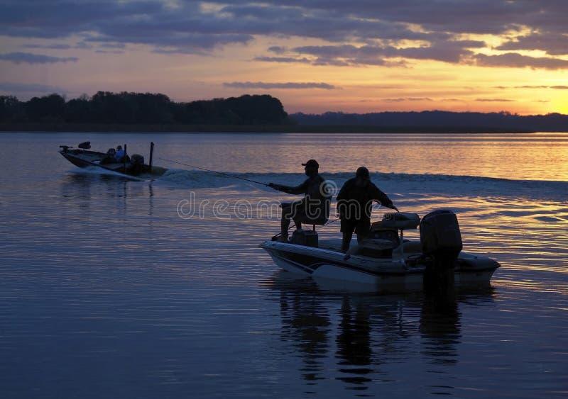 前往现出轮廓的渔夫钓鱼,太阳在美好的日出出来 免版税库存照片