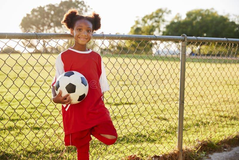 前拿着足球的青少年的黑人女孩看对照相机 免版税库存照片
