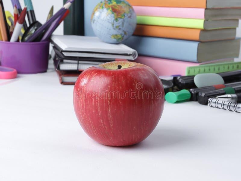 前景在学校用品背景的红色苹果计算机  与拷贝空间的照片 图库摄影