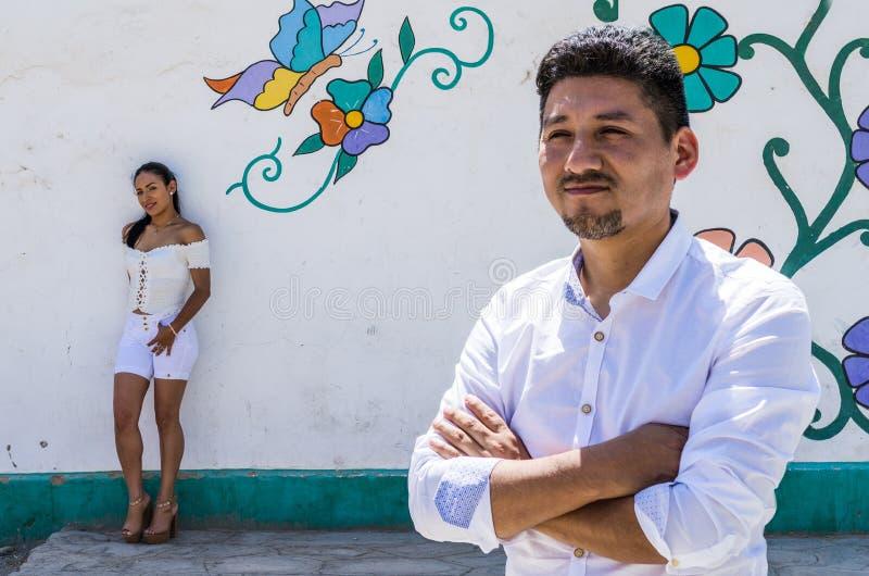 前景的人与女朋友在基于五颜六色的墙壁的背景中 免版税库存图片