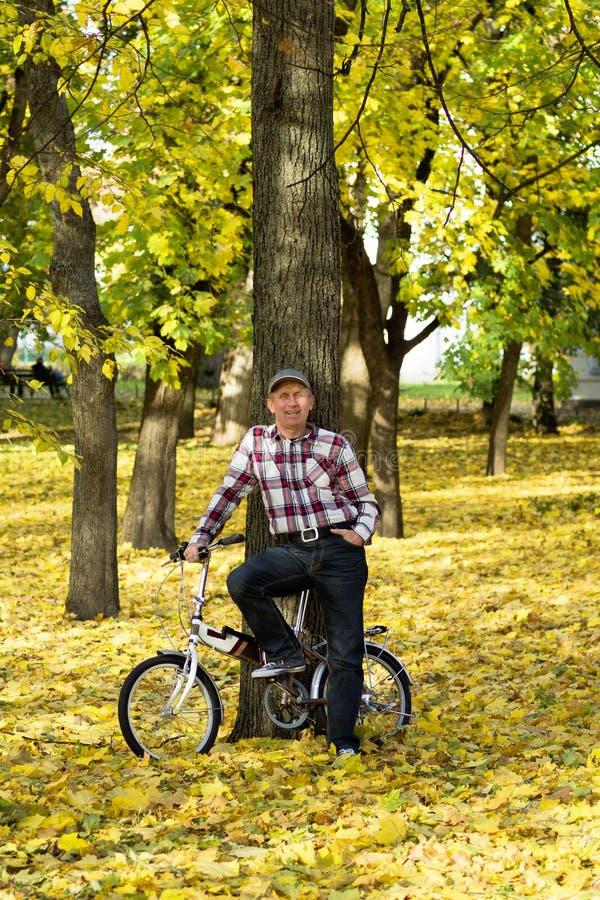 前辈和他的自行车在秋天公园 免版税库存照片