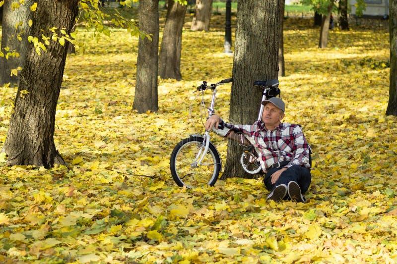 前辈和他的自行车在秋天公园 免版税库存图片