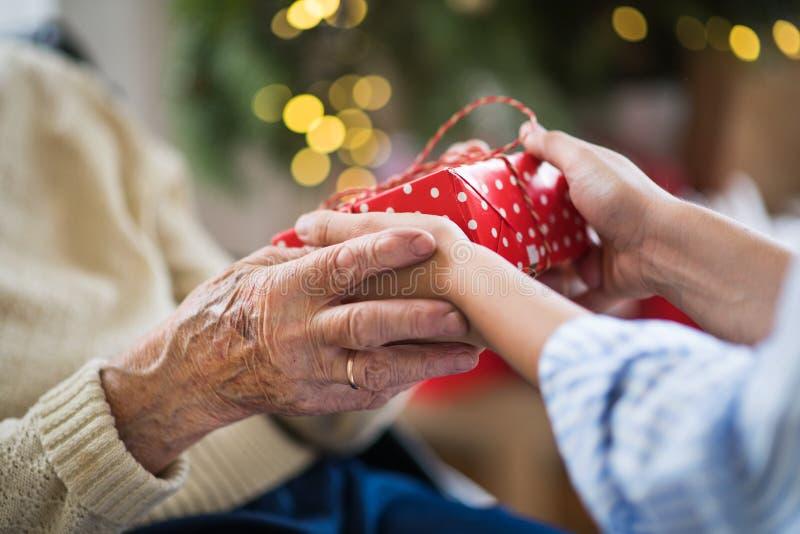 前辈和年轻女人的手特写镜头拿着礼物的在圣诞节 免版税图库摄影