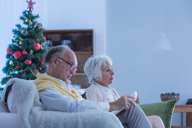 前辈坐长沙发在圣诞节期间 免版税库存照片