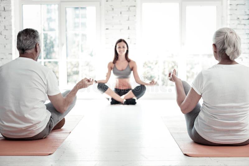前辈思考在瑜伽类期间的已婚夫妇 免版税图库摄影