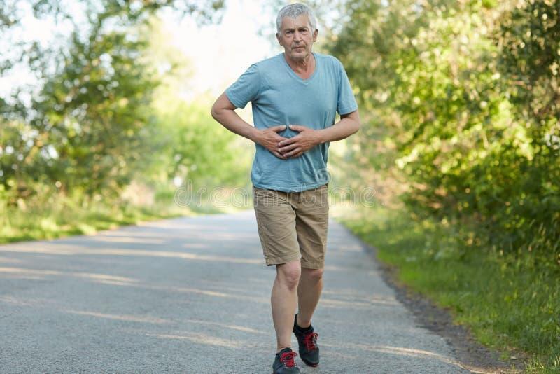 前辈照片起了皱纹男性接触胃,有痛苦,在报道长途在早晨跑步期间,穿戴在运动服, ha后 免版税库存图片