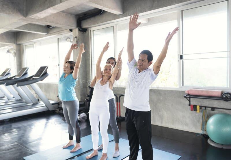 前辈的小组朋友有愉快的教练员的在瑜伽健身房微笑和 年长健康生活方式 图库摄影