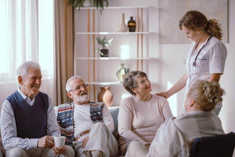 前辈谈话与护士在养老院 免版税库存照片
