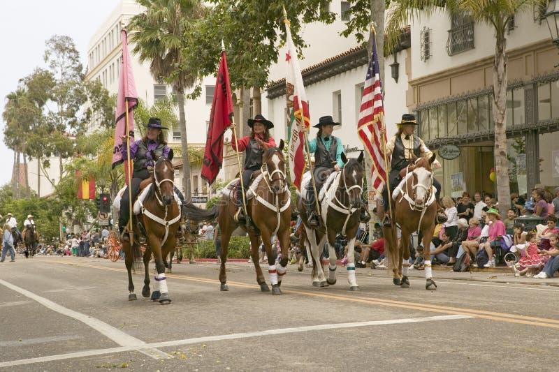 前进与美国人和加利福尼亚旗子的牛仔被显示在营业日期间游行在举行的每年老西班牙几天节日前夕 免版税图库摄影
