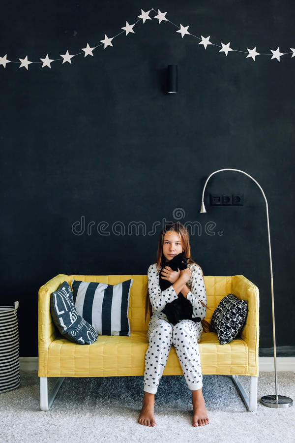 前长沙发的青少年的孩子对在现代生活的黑墙壁 图库摄影