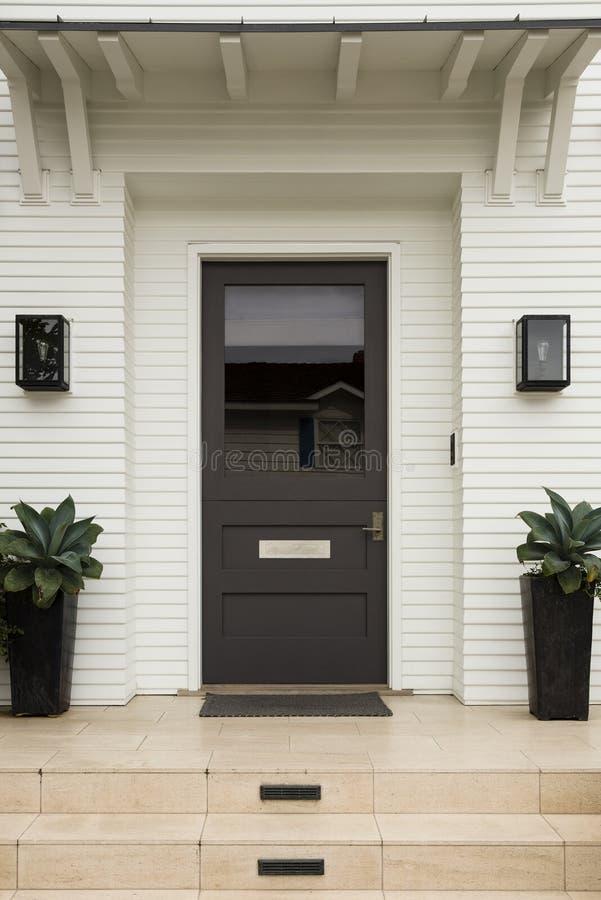 前门,棕色门,白色外部 免版税库存图片