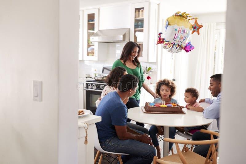 前青少年的女孩在与她的庆祝她的生日的三一代家庭的厨房用桌上,吹灭蜡烛坐她的b 库存照片