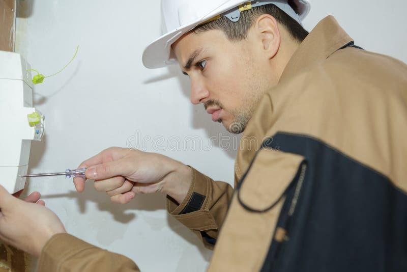 前面保险丝交换机板的年轻电工工程师工作者 免版税库存图片