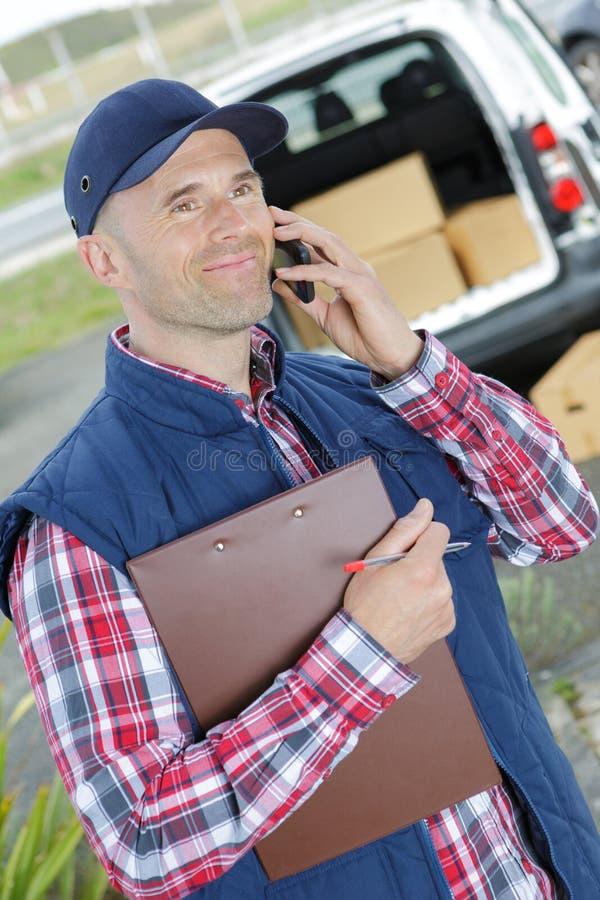 前面卡车的愉快的男性工作者谈话在手机 库存图片