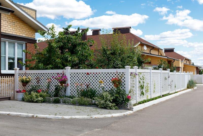 前面庭院的白色滤网篱芭在一个郊区村庄 免版税库存图片