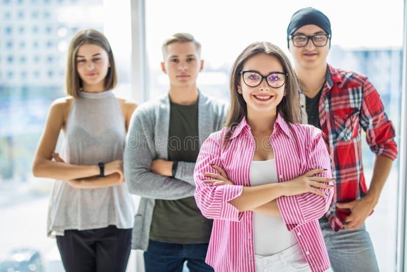 前面的严肃的学生妇女与胳膊折叠了在全景窗口前面的身分 免版税图库摄影