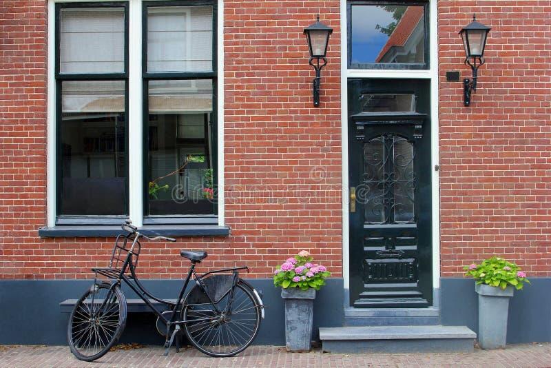 前面老荷兰房子窗口门砖墙葡萄酒自行车墙壁,荷兰 免版税库存图片
