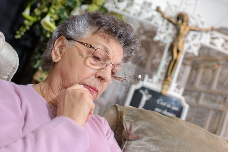 前面耶稣受难象的年长妇女 库存图片