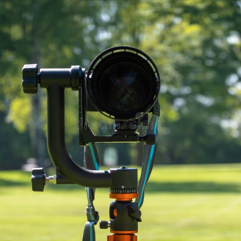 前面被射击一个大远摄镜头在有手工重的常平架的,故意地被弄脏的背景一个三脚架登上了户外, 库存照片