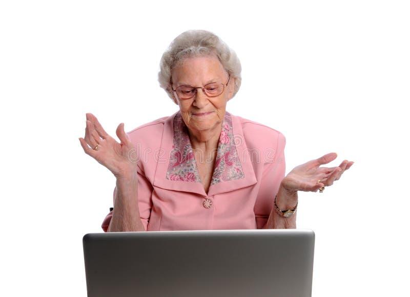 前面递膝上型计算机高级投掷的妇女 图库摄影