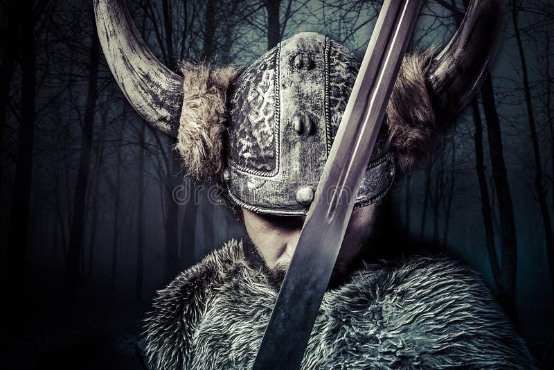 剑,有盔甲的北欧海盗战士在森林背景 库存图片