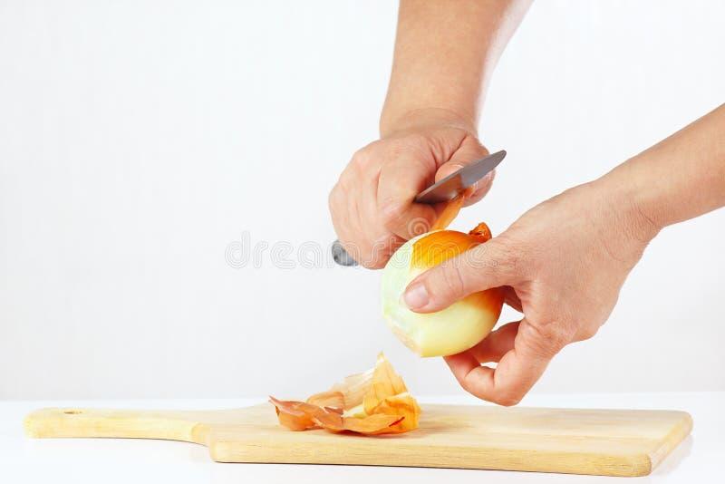 剥与刀子的手新鲜的葱 免版税库存照片