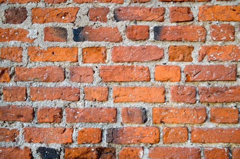 剥长方形红色橙色明亮的砖的被抓的墙壁老古老中世纪古色古香的健壮的石头的纹理 库存图片