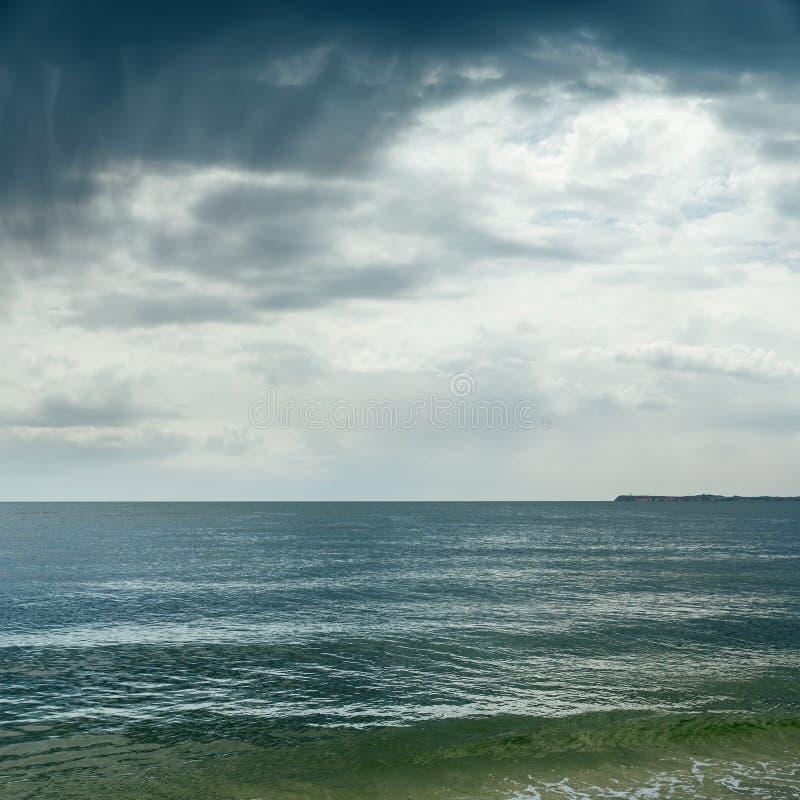 剧烈的云彩使海变暗 图库摄影