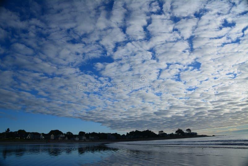 剧烈的云彩暂停在新英格兰海滩 免版税库存图片