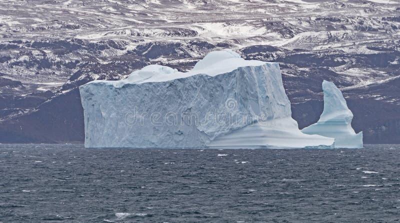 剧烈的大冰山在离格陵兰的海岸的附近 免版税库存图片