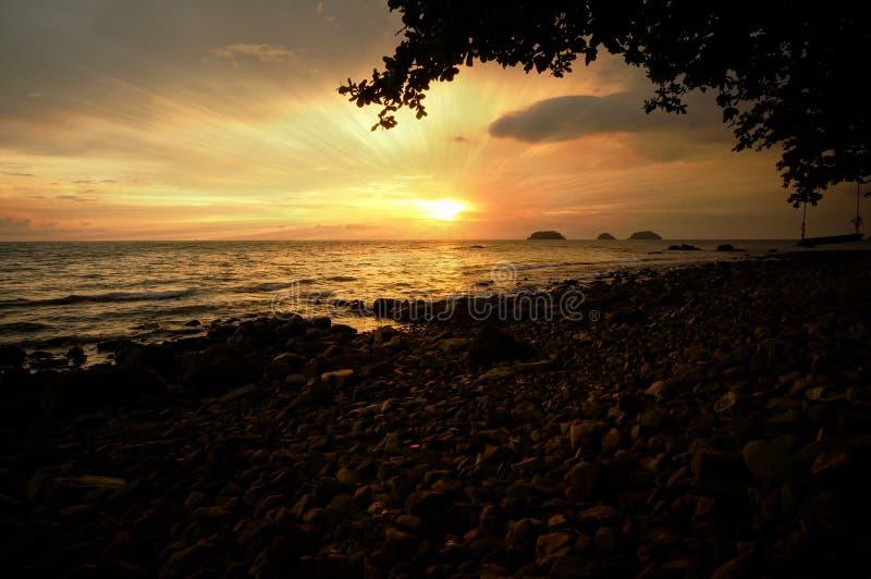 剧烈的日落和太阳在海放光 免版税库存图片