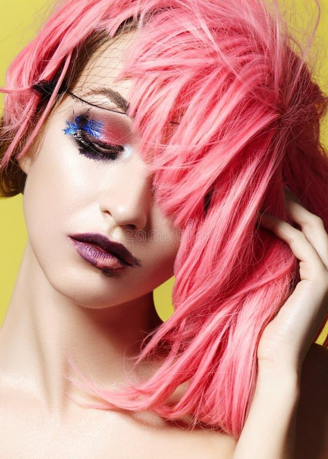 剧烈的桃红色假发的时尚看起来少妇 与明亮的构成的美好的模型 狂欢节辅助部件为万圣夜 免版税库存照片