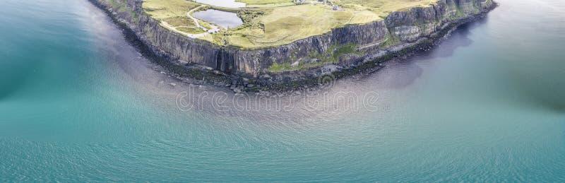 剧烈的海岸线的电影空中射击在峭壁的接近著名苏格兰男用短裙岩石瀑布,斯凯岛 免版税库存图片
