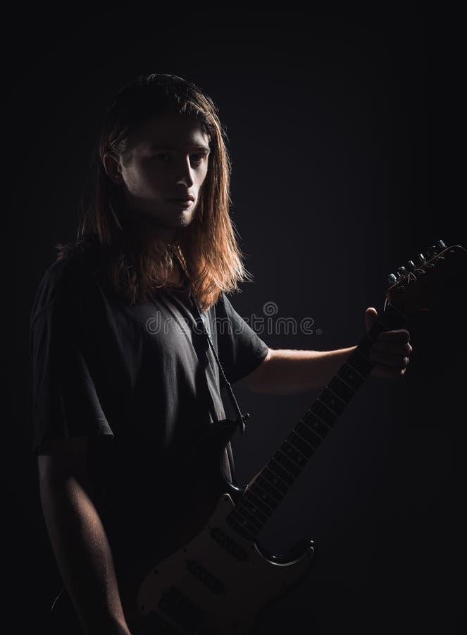 剧烈的演播室画象:英俊的长发年轻人岩石音乐家在手上拿着电吉他 库存图片