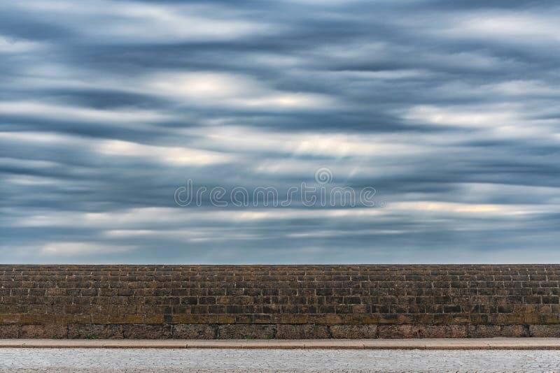 剧烈的风雨如磐的天空的图片与云彩的在石墙 免版税库存图片
