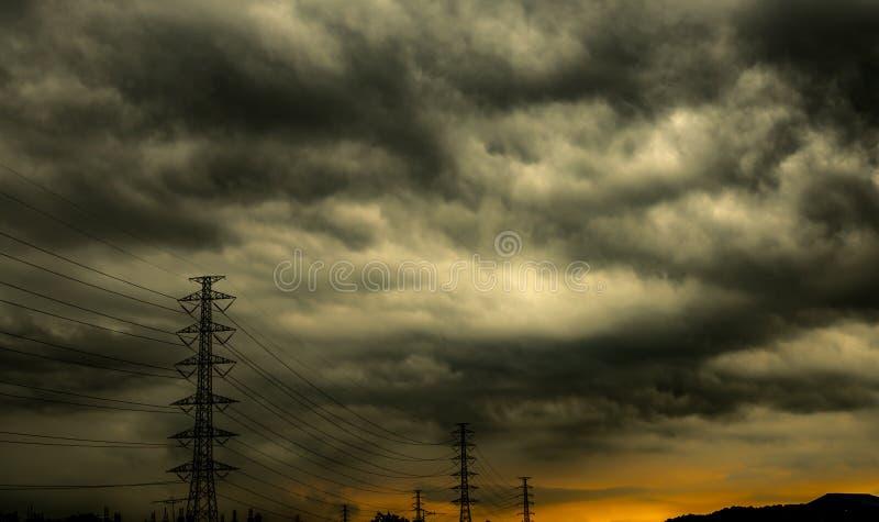 剧烈的黑暗的天空和云彩和高压杆与电缆 背景多云天空 在雷暴前的黑天空 免版税库存照片