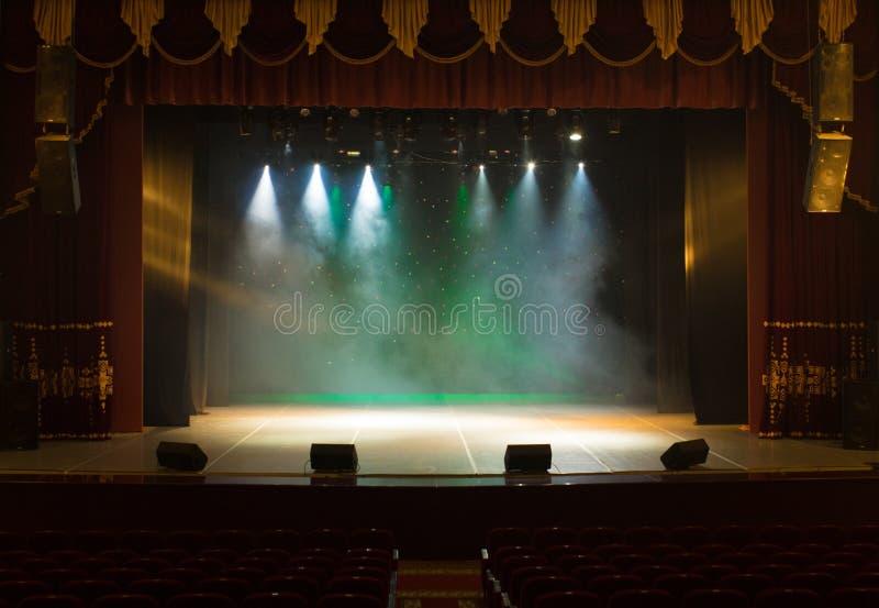 剧院的一个空的阶段,点燃由聚光灯和烟 免版税图库摄影