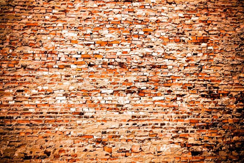 剩余水泥和灰色油漆部分盖的老和被风化的脏的红色橙色砖墙当纹理背景用轻微vi 免版税图库摄影