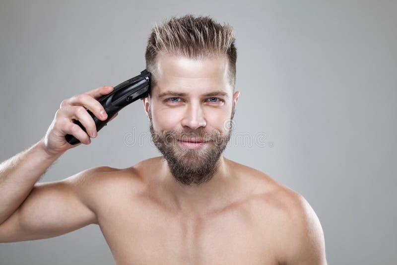 剪他有飞剪机的英俊的人自己的头发 库存照片