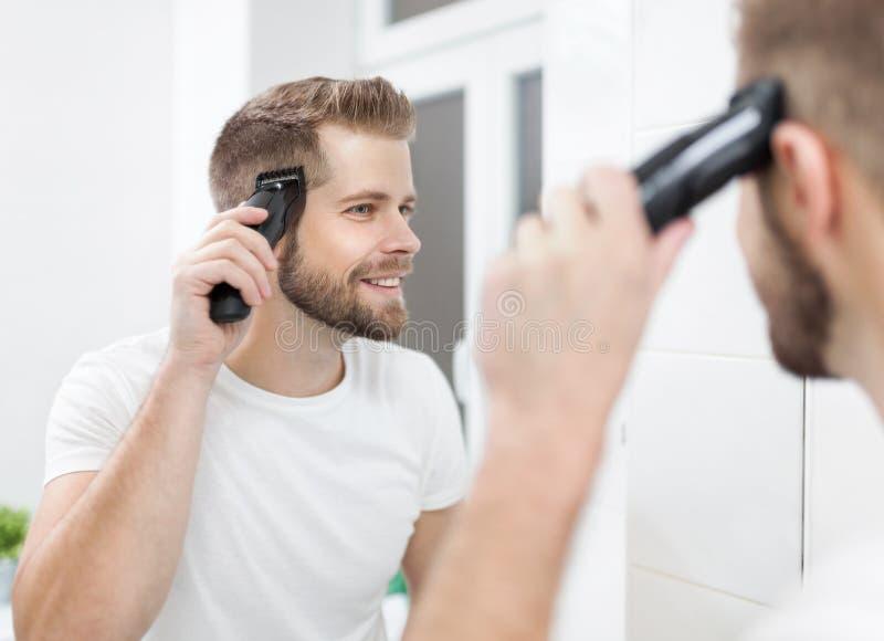 剪他有飞剪机的英俊的人自己的头发 免版税库存照片