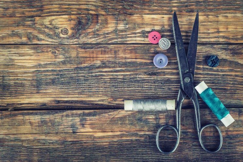 剪刀、片盘有螺纹的和针 在老木背景的老缝合的工具 免版税库存图片