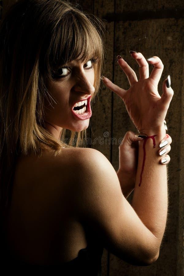 剪切危险女性她的吸血鬼腕子 免版税库存图片