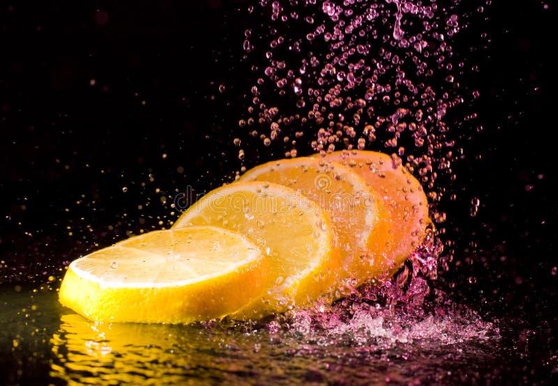 剪切柠檬飞溅在水之下 免版税图库摄影